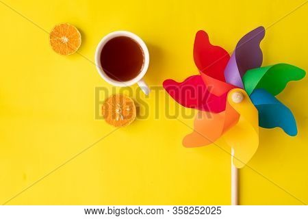 Cup Of Tea And Sliced Orange And Colorful Pinwheel.