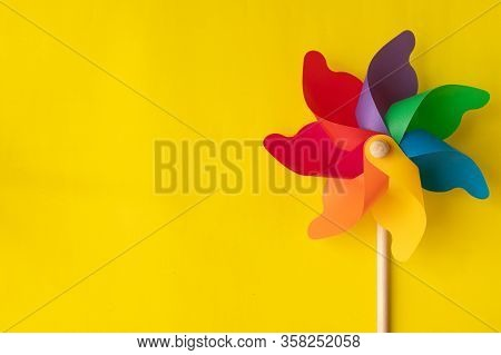 Copy Space With Colorful Pinwheel On Yellow Background.