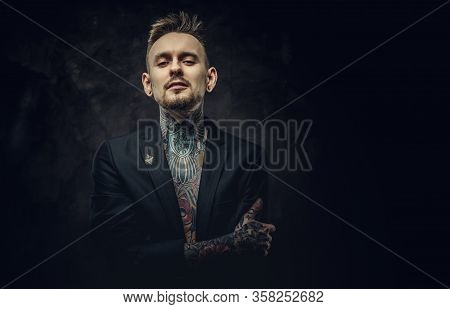 Seductive Looking Tattoo Artist Posing On A Dark Background Wearing A Black Tuxedo On A Half-naked B
