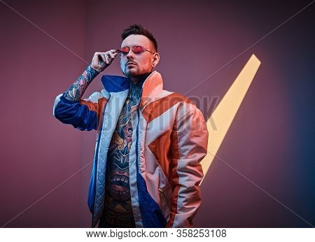 Extravagant Male Model Tattoo Artist Posing In A Neon Studio Wearing Racer Coat On A Half-naked Body