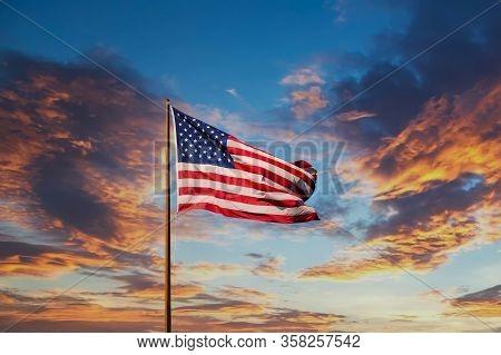 An American Flag Against A Blue Sky On An Old Rusty Flagpole
