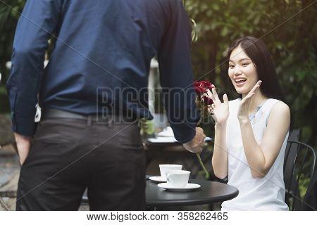 A Man Is Proposing Marriage To A Smiling Woman With A Lovely Flower Bouquet In A Beautiful Garden, L