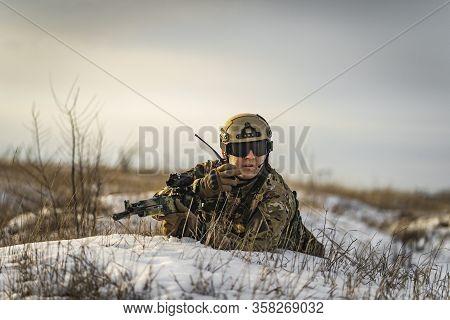 Modern War Soldier Army Man In Multicam Camouflage Is Lying In Winter Field And Speaks On The Walkie