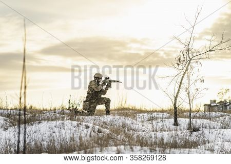 Modern Soldier In The Winter Multicam Camouflage Is Patrolling Or Patrol Field Territory. Full Equip