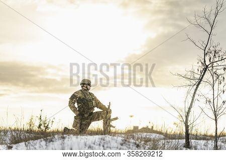 Modern Soldier In The Winter Desert Put Gun On The Ground And Knelt Down. Full Equipment Commandos W