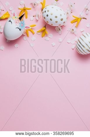 Easter Eggs In The Form Of A Unicorn And Eaggs With Gold Pattern On Pink Background With Flowers. Ha