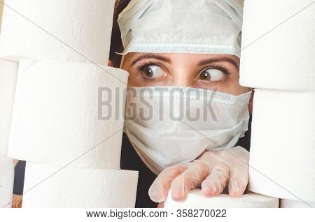 Young Woman With Scared Eyes In Two Medical Virus Protection Face Masks Looks Through Stacks Of Toil