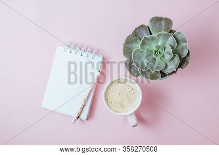 Morning Pink Coffee Cup, Clean Notebook, Pen, And Flower In Pot On Pink Background. Planning And Des