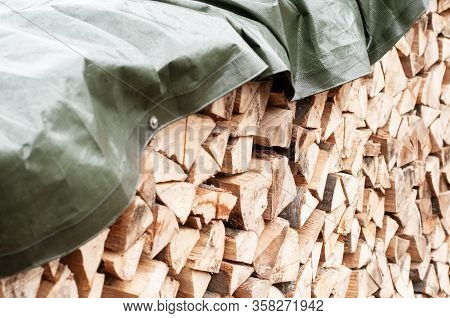 Close-up Of A Stack Of Chopped Firewood Covered With A Tarpaulin