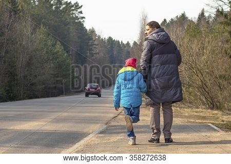 Woman In A Jacket Holds A Child By The Hand. Near The Road, In Proportion Passing Car