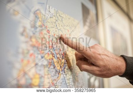 Close-up Of Hand And Finger Pointing Region On Atlas Map