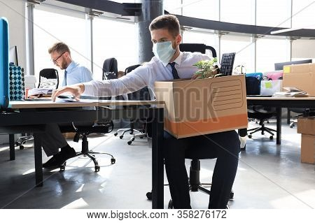 Dismissal Employee In An Epidemic Coronavirus. Sad Dismissed Worker Are Taking His Office Supplies W