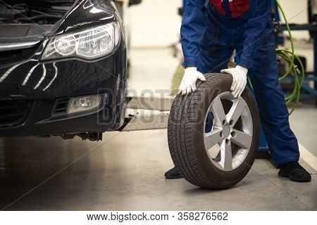 Mechanic Holds Tires At The Garage. Changing Tires In A Car Service Center In Asia
