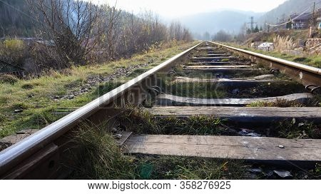 Close Up Perspective View Of Railway Tracks On A Bright Sunny Day. Rails And Wooden Sleepers In Oil