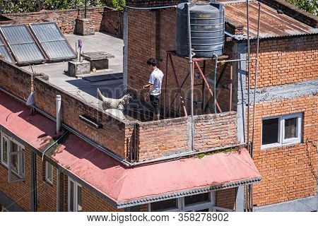 Kathmandu, Nepal - March 29, 2020: A Man Plays With His Dog On A Rooftop. People Are Finding Ways To