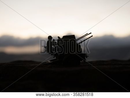 An Anti-aircraft Cannon And Military Silhouettes Fighting Scene On War Fog Sky Background, World War