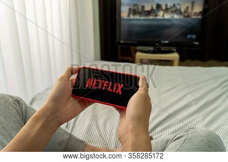 Bangkok, Thailand - March 27, 2020: Man Sitting On Bed In Bedroom Holds Netflix Logo On Smart Phone