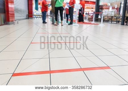 Social Distancing Being Practiced At Entrance To Supermarket, With 1 Meter Gap Between People In Que