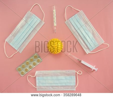 Medical Disposable Masks, Thermometer, Syringe And Pills On A Pink Background Surround The Coronovir