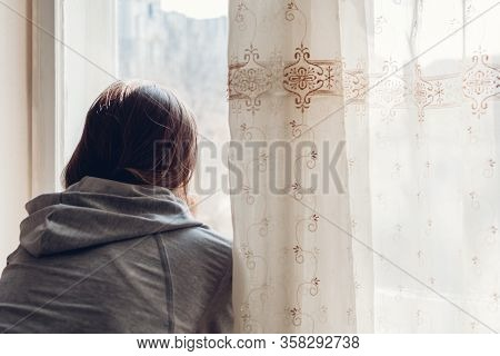 Isolation At Home During Coronavirus Covid-19 Pandemic. Woman Looking At Window. Stay Safe At Home O