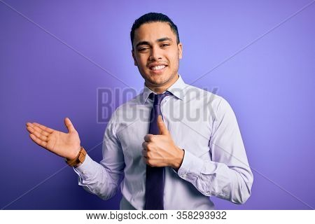 Young brazilian businessman wearing elegant tie standing over isolated purple background Showing palm hand and doing ok gesture with thumbs up, smiling happy and cheerful