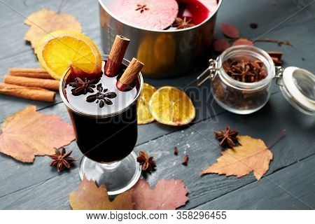 Mulled Wine. Glass Of Winter Hot Drink With Citrus, Apple And Spices. Stewpan With Mulled Wine And C