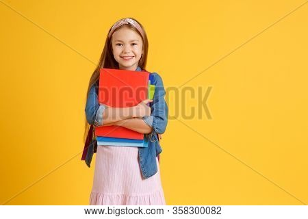 Portrait Of Happy Caucasian School Girl With A Book. Beautiful Positive Girl With Long Red Hair Stan