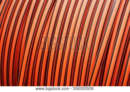 Close-up Of Orange And Black Broadband Cable On A Cable Drum, Full Frame