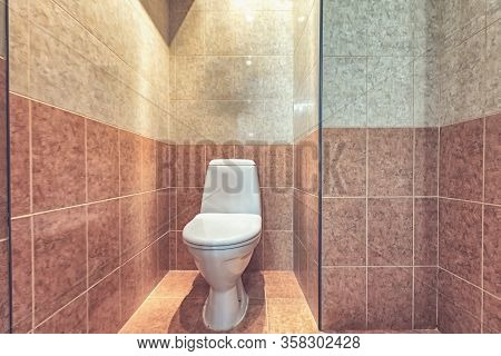 Toilet Bowl In The Toilet Room. Restroom With Beige Tile Decoration And Flooring