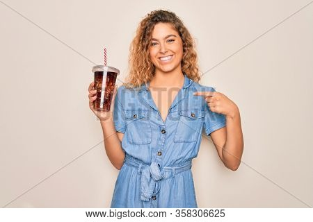 Beautiful blonde woman with blue eyes drinking cola beverage using straw to refreshment with surprise face pointing finger to himself