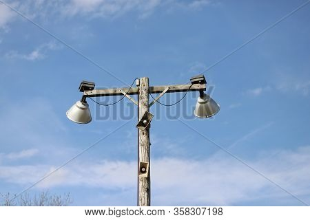 A Floodlights   On A  Football Field  Against Blue Skies