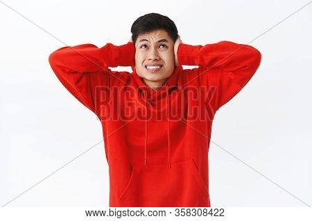 Waist-up Portrait Of Asian Man In Discomfort, Distressed And Annoyed, Looking Up Angry At Neighbours