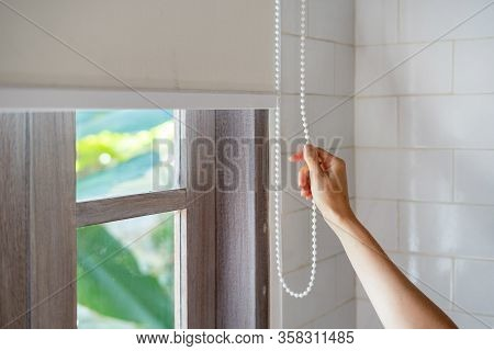 Concept Of Lighting Range Control. Cropped View Of Woman Pull Rope And Closed Modern White Jalousie