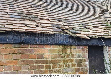 Damaged Clay Roof Tiles On A Pitched Roof On A Derelict House In England, Uk