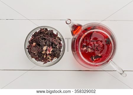 Red Tea, Brewed In A Transparent Teapot.dry Tea Leaves, White Background.the View From The Top.