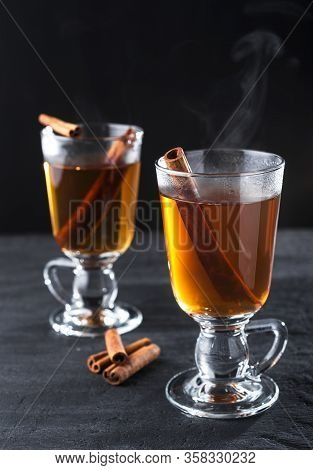 Freshly Brewed Black Tea With Cinnamon, In Transparent Cups On A Dark Background.