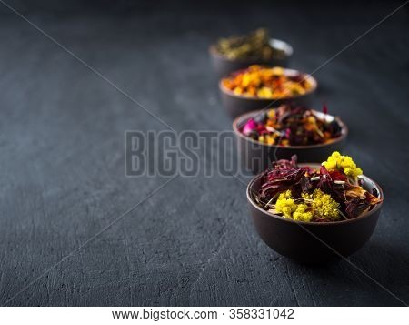 Set Of Different Herbal And Fruit Dry Teas In Clay Bowls, Dark Moody, Stone, Concrete Background.