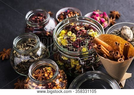 A Set Of Various Herbal And Fruit Teas In Glass Jars On A Dark Background. Medicinal Herbs. A Natura