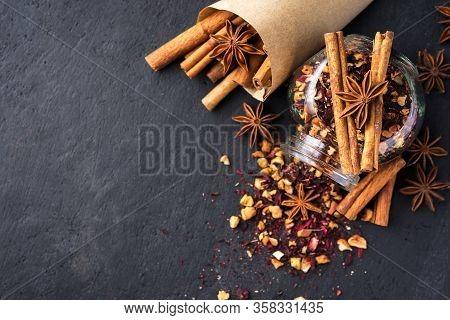 Tea Leaves In A Glass Jar, Cinnamon Sticks And Anise On A Dark Background.dark Mood.