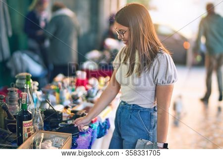 Young beautiful woman smiling happy and confident. Standing with smile on face looking a jumble sale at the town street