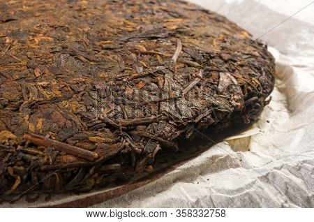 Chinese Pressed Puer Tea On Wrapping Paper, Close-up, Macro