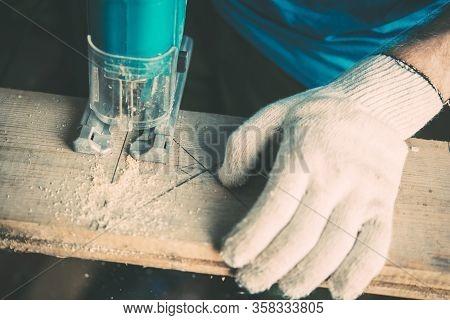 Male Carpenter Sawing Wood Gloss Using A Jigsaw