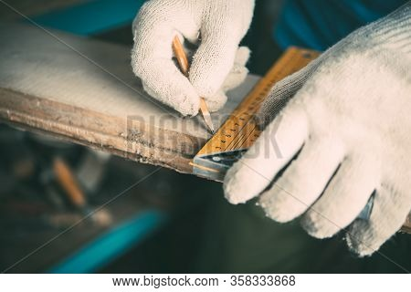 Male Worker Measures The Length With A Metal Ruler-corner On A Wooden Board, Carpentry