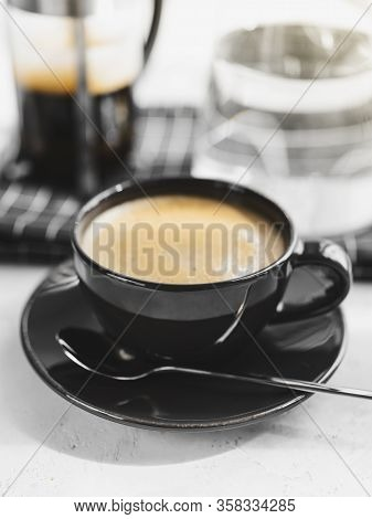 Coffee In Black Cup On White Background, Table. French Press, Carafe Of Water, Napkin, Sunlight. Bre