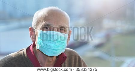 Old Man In Protective Face Mask Anti Virus Looks In Camera Window Background