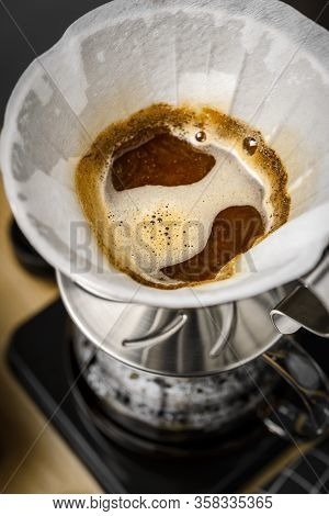 The Process Of Brewing Coffee In Pour Over, Filter Coffee, A Glass Teapot On A Wooden Tray On A Dark