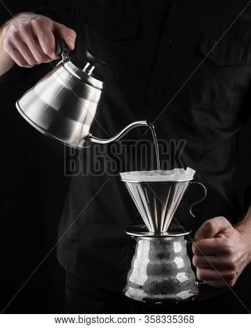 A Barista Brews Coffee By An Alternative Method In Pour Over, Coffee Filter, Glass Teapot On A Woode