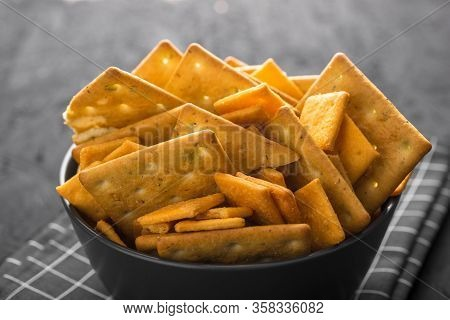 Black Bowl With Crackers On A Dark Concrete Background