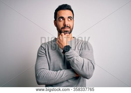 Young handsome man with beard wearing casual sweater standing over white background with hand on chin thinking about question, pensive expression. Smiling with thoughtful face. Doubt concept.
