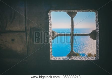 Old Wrought-iron Black Door And A Metal Grating On The Window With A View Of The Blue Sea Outside, T